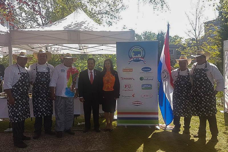 El embajador Fernando Ojeda Caceres y señora, junto al equipo de Asado Benítez posando ante el banner donde se promociona las marcas de carne paraguaya.