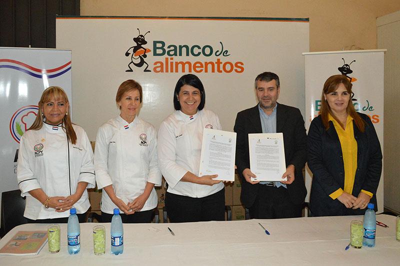 Teresita Benegas O´Hara, presidenta de la Asociación de Chefs del Paraguay y Guillermo Fanego, titular de la Fundación Banco de Alimentos, muestran el convenio firmado. Acompañan Marietta Villamayor y Miryan Vera, de la Asociación de Chefs y Fátima Díaz de Vivar, vice presidenta del Banco de Alimentos