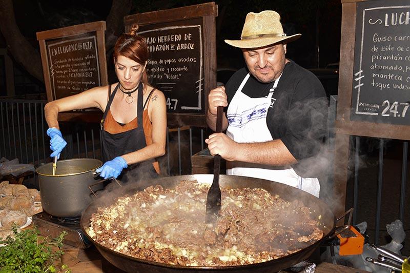 Luchef revolviendo con la pala lo que terminará siendo su famoso guiso carretero. A su lado, Majo Herrero preparando una sopa con papas asadas.