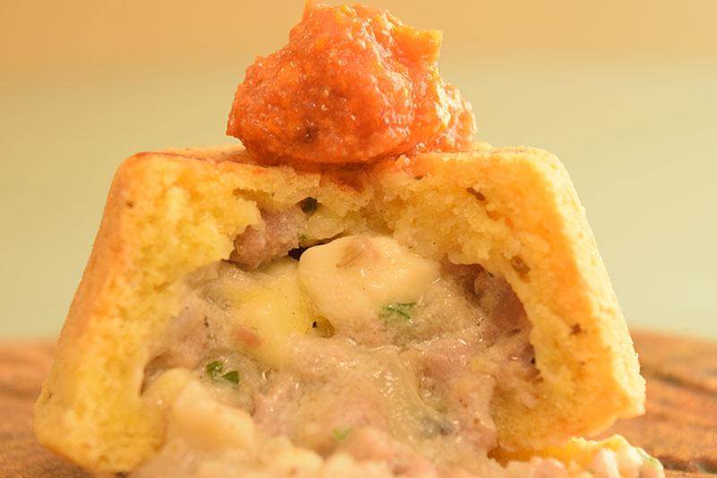 Primer plano de la chipa Chutita que lleva un relleno de carne y queso y se presenta en forma de volcán.