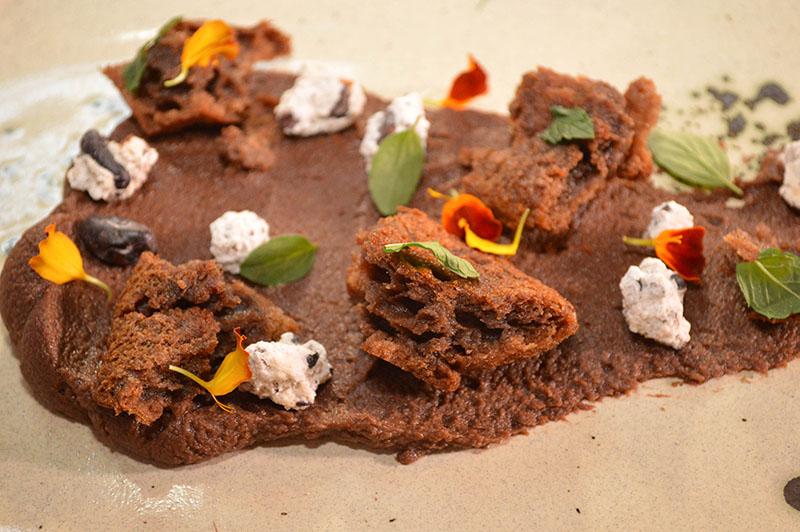 El postre lleva productos provenientes todos de la amazonia bolivia. En la base del plato un ganache de chocolate, los trozos son como una masa intermedia entre el flan y el bizcocho, adornados con garrapiñadas de granos de café.