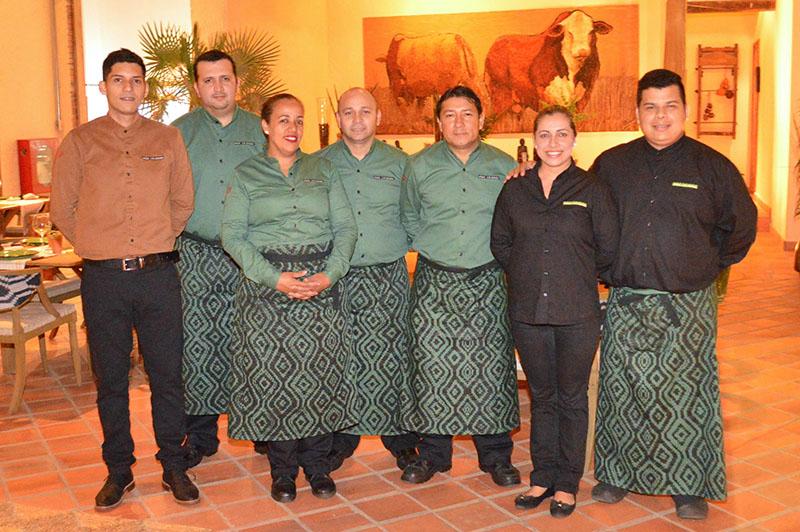 El equipo de servicio, con delantales elaborados con tejidos indígenas. Y al fondo otra imponente obra de Koki, un homenaje al ganado del Chaco.