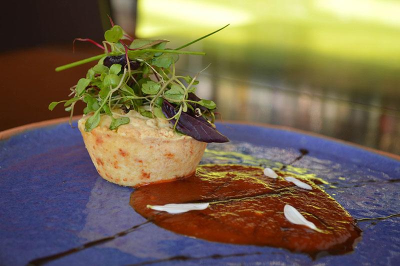 Mbeju avevo relleno con queso Camembert y muzarella. Mermelada de locotes rojos, toque de picante y ensalada de brotes vegetales. Sobre un colorido plato de Mango Rojo.