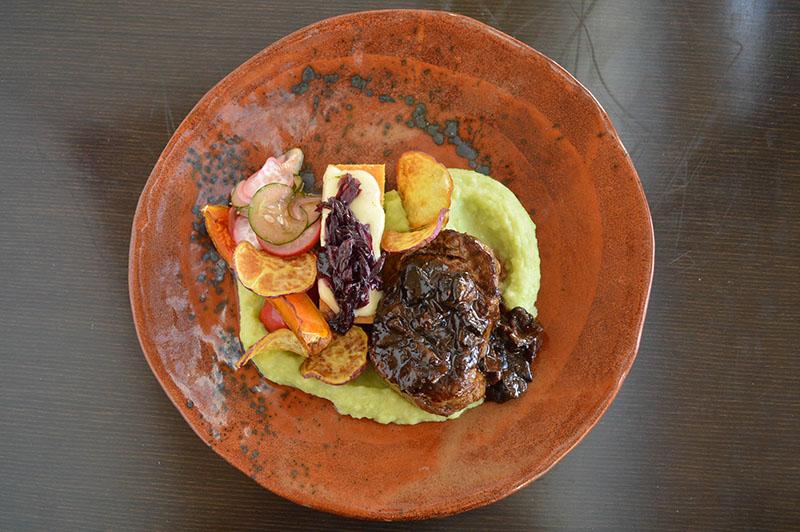 Lomito en corte churrasco, con sopa paraguaya con queso de cabra, acompañado de verduras de estación en diferentes texturas, cebolla caramelizada, y una salsa de shiitakes, caña y miel.