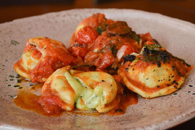 Ravioles caprese, de elaboración casera, rellenos con muzzarella. La salsa está preparada en un salteado de cherry, oliva, tomate y albahaca. La masa lleva en su composición un poco de albahaca para intensificar el sabor.