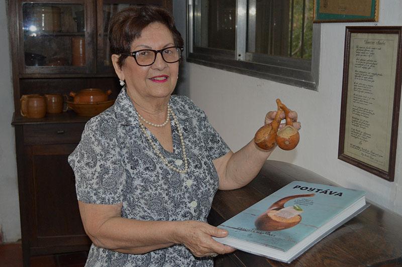 Graciela Martínez en una de manos exhibe su libro Poytáva y en la otra sostiene un utensilio utilizado por nuestros ancestros.