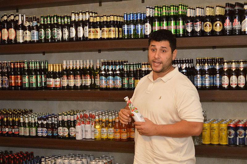 Jaime Peña González mostrando algunas de las tantas variedades de cervezas importadas que tienen a la venta.