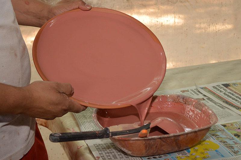 Un plato que está en proceso de esmaltado. El tinte que vemos se transforma en otro color después del proceso de horneado. Y nunca se sabe que color finalmente tendrá el plato.