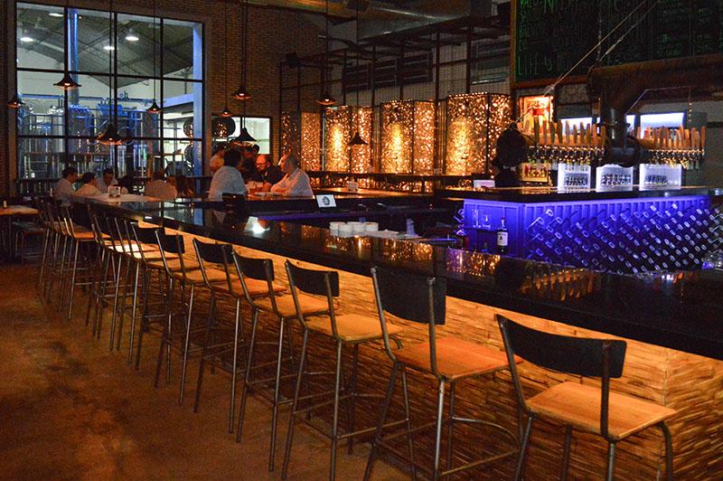 Al fondo se ve la micro cervecería de cerveza. En el primer plano una gran barra en cuyo centro se ubican las canillas que proveen la bebida.