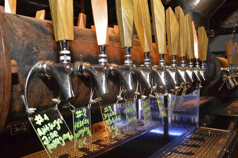 Cuarenta canillas tiene Palo Santo. Solo están habilitadas 28 y de ellas 6 con cervezas de la casa. Llegan hasta la barra ubicada en el centro del bar a través de un sistema de tuberías que transporta la cerveza ubicada en la cámara fría que está a unos 15 metros.