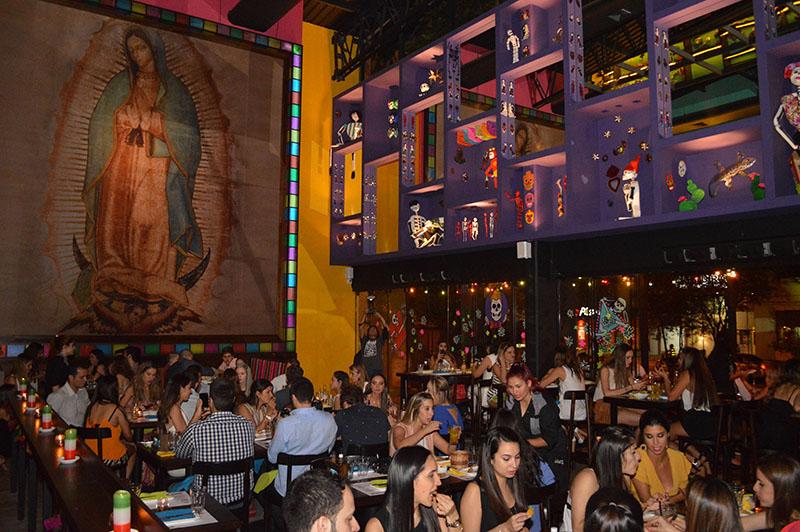 Una inmensa imagen de la Virgen de la Guadalupe domina el salón de Lupita. Colores chillones y objetos de la imaginería religiosa mexicana adornan el local.