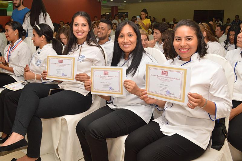 Egresadas del primer año muestran los certificados que los acreditan como Asistentes de Gastronomía, durante uno de los actos de colación en el Centro Garofalo.