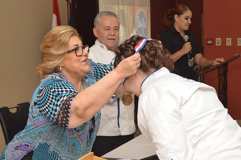Sarita Garofalo entregando una medalla a una de las ganadoras del Concurso de Cocina María Clara Benza de Garofalo, que cada año realiza la institución.