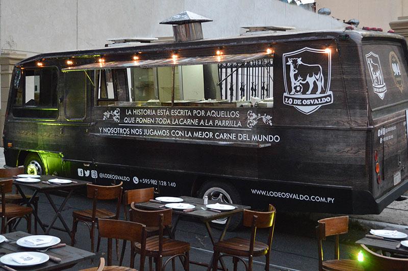 Primer plano del Food Truck. En el interior está equipado convenientemente y afuera se puede la disposición de las mesas y sillas, que también forman parte del servicio.