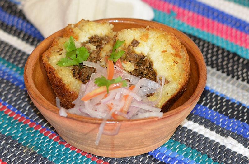 Aquí se fuionan la mandioca como producto oriundo y la técnica del salteado de carne como relleno, acompañas con la salsa criolla, sin olvidar el toque de sabor del ají panca.