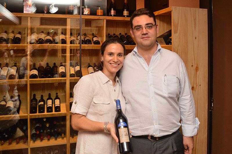 Bettina Torres y Jean-Philippe Bierre, el matrimonio propietario de Le Parisienne. Ella mostrando uno de los mejores vinos de la vinoteca. Atrás se ve el espacio especial destinado de las etiquetas Premium.
