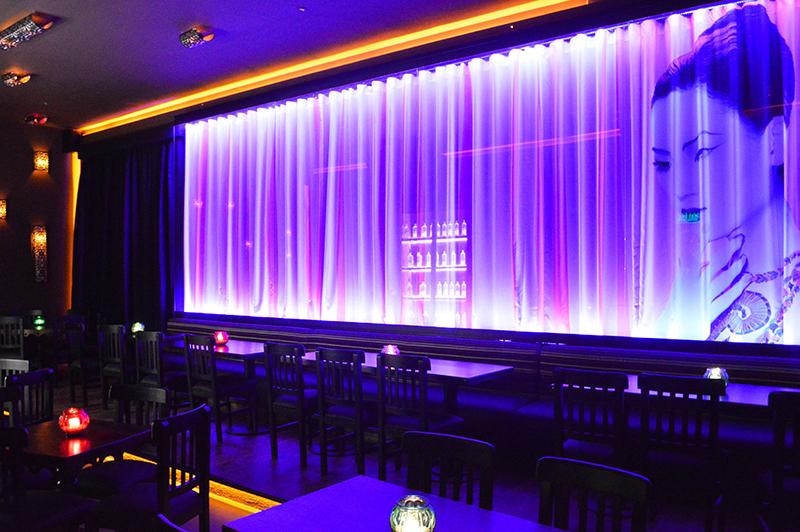 Parte del salón privado de Taj. Una gran cortina con la imagen impresa de una geisha. Es como una postal de los bares Taj.