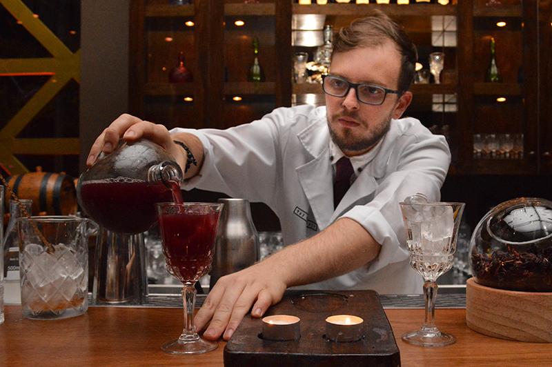 El bartender vestido con guardapolvo blanco, preparando el Blood Bank, que lleva vodka, oporto, jengibre, naranja, y biter Angostura.