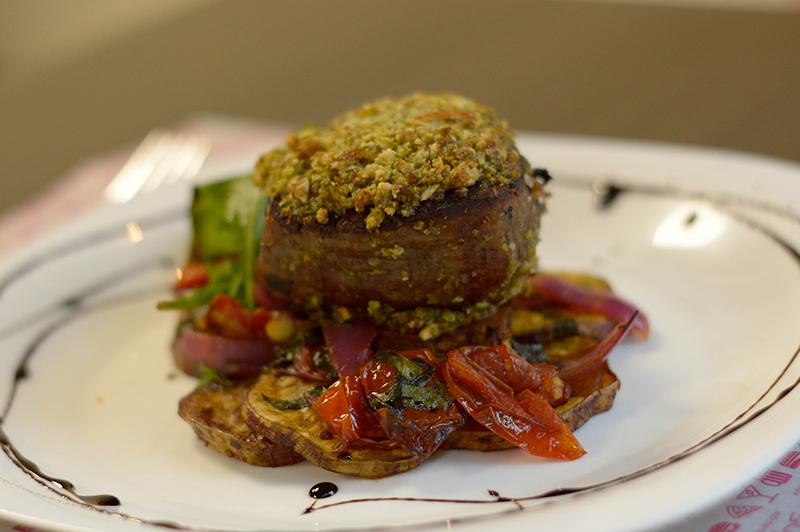 Lomito con Costras de Frutos Secos, que lleva perejil, batata horneada, espinaca, tomates y cebollas asados.
