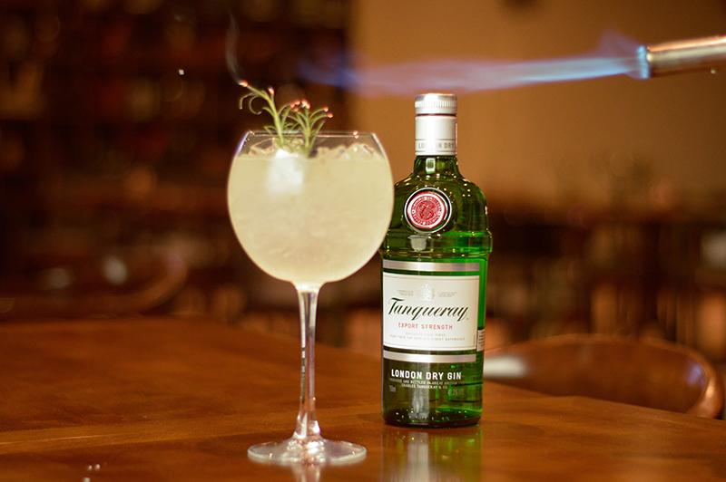 El gin tónic clásico lleva una medida de Tanqueray, hileo y agua tónical. A veces un twist de limón. En esta versión el barman le agregó un poco de romero que fue sopleteado para avivar su aroma.
