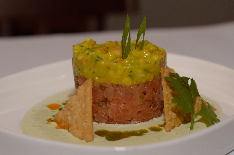 Tartar de salmón. Estilo asiático, aromatizado con aceite de sésamo tostado, palta, emulsión de cilantro y crackers de trigo.