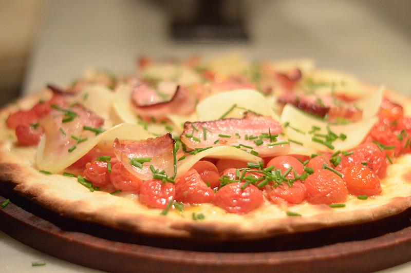 La versión de otoño de El Almacén de Pizzas. Un primer plano donde se aprecian todos sus ingredientes. Tomatitos enteros asados, láminas de papa, panceta y queso.