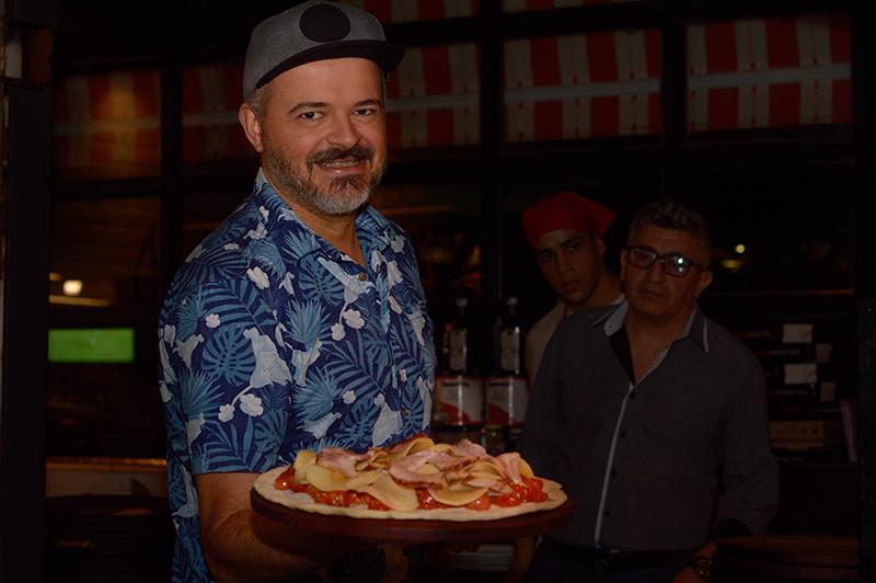 El Gordo exhibiendo su pizza de otoño. Pueden verse las láminas de papa, los tomates casi enteros a poco de entrar al horno.