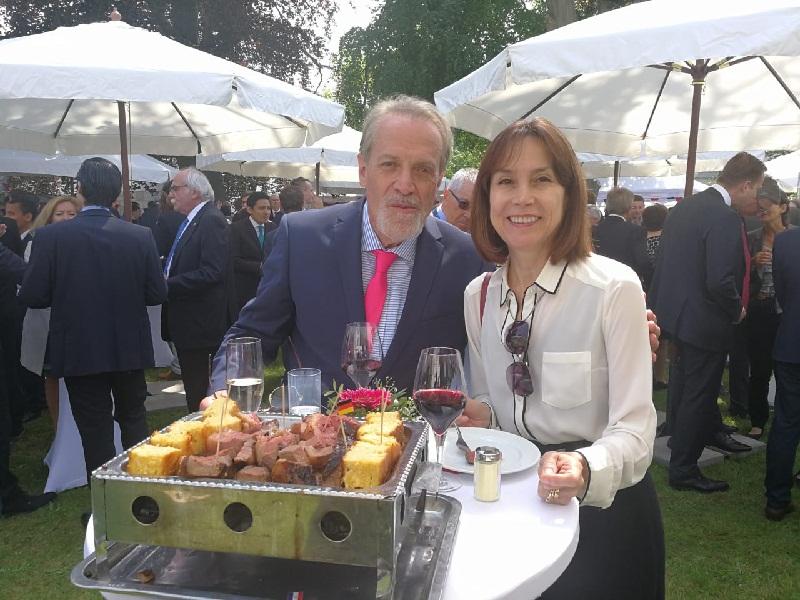 Dos de los invitados a la Fiesta Paraguaya en Berlín, posando junto a la famosa parrillita, todo un símbolo de la gastronomía paraguaya.
