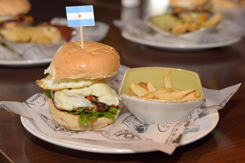 Tango Salsa Burger que representa a Buenos Aires. lleva rodajas de salchicha, salsa criolla, salsa alioli, queso Monterrey Jack, rúcula fresca y huevo frito.