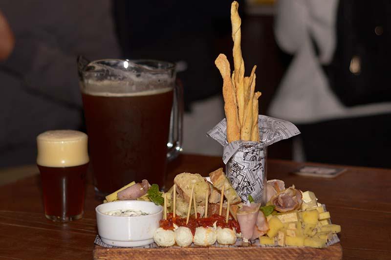 La cerveza Mensualero, jarra y vaso, aparecen junto a una nutrida tabla de quesos variados, jamones, pan ciabatta y palitos.