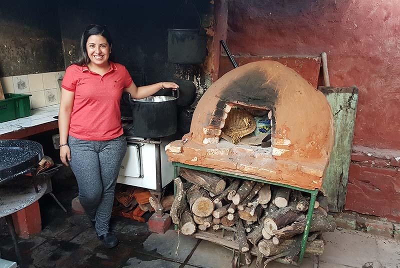 María Liz junto a los elementos de cocina en el fondo de su casa. Un tatakuá, una cocina a leña y a la derecha asoma una especie de paellera. No entraron en el cuadro, las parrillas y el disco de arado.