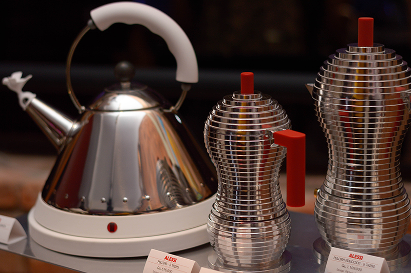 A la izquierda la cafetera Alessi, el producto más vendido de la marca. Tiene un mango colorido para indicar donde debe ir la mano y un pájaro en el pico. La forma cónica permite que pueda alcanzar altas temperaturas en poco tiempo.