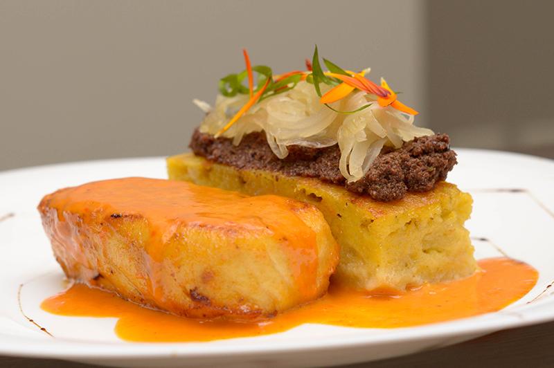 Surubí al horno en salsa de locote rojo y alcaparras, acompañado de sopa paraguaya, tapenade de aceitunas y cebolla caramelizada.