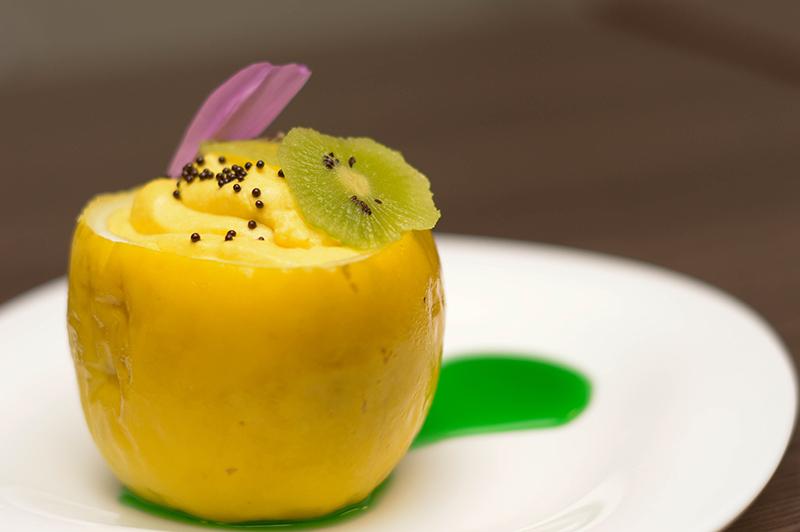 Una cáscara de mburucuja sirve de recipiente a un dulce de calabaza coronado con rodajas de kiwi,