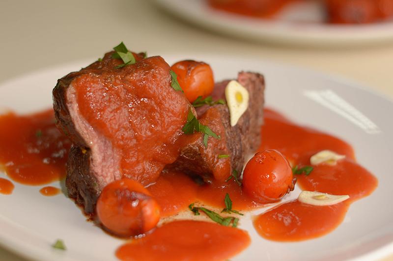 Un lomito de res con salsa de tomate y tomates cherrys asados con lascas de ajo.