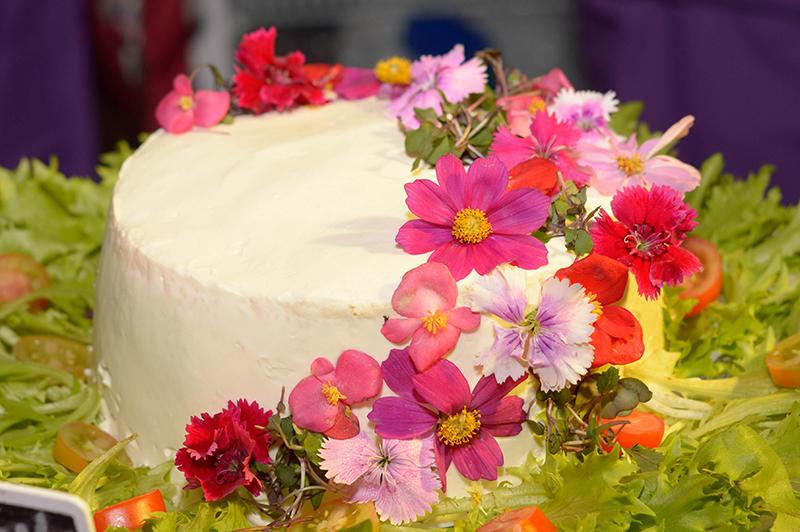 la vista luce como una torta decorada con flores comestibles, como muchas que se ofrecen en el mercado. Pero su interior revela un contenido diferente. Porque se trata de una ensalada con forma de torta.