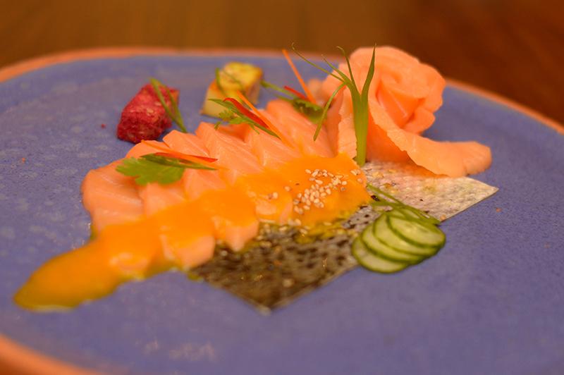 Una de las entradas frías sera el tiradito de salmón en salsa de ají amarillo con un poco de palta a la parrilla, algo nuevo que se está y cae bastante bien al plato.