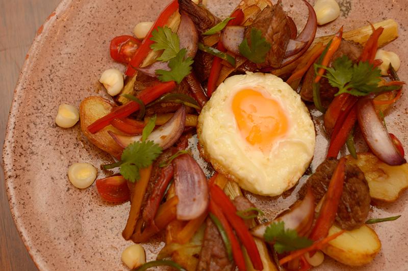 Un lomo saltado a lo pobre. Carne de res salteada al wok con diversas verduras, acompañado de papas y mandiocas fritas.