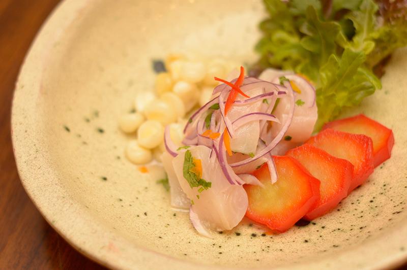 El ceviche de pescado acaompañado de choclos peruanos al anis y camote glaseado con jugo de naranja.