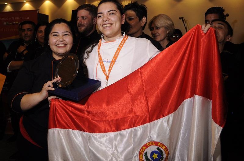Jessica Fariña Rojas, a la derecha, aparece junto a su profesora y tutora Marlene Grance, tras recibir el primer premio en el concuro Inter Igi realizado en Rosario, Argentina.
