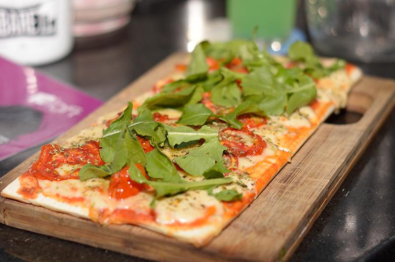 La pizza de muzzarella, salsa de tomate, tomate seco y rúcula, una de las tantas opciones gastronómicas. Tambien hay picadas y sandwiches.