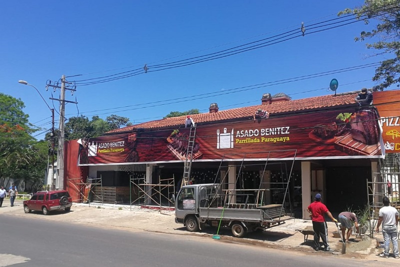 Sorprendimos a los trabajadores, en el momento en que estaban colocando el gran cartel para la parrillada de Asado Benítez, sobre Aviadores del Chaco.