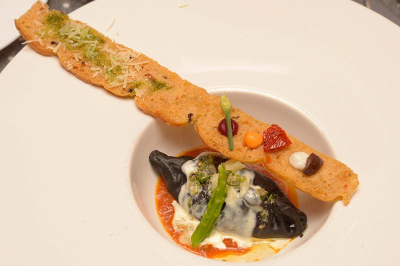 Esto es Culurgione al Nero di sepia. Una pasta pintada con tinta de calamar y que iba rellena con camarones, con salsa de tomates asados a la leña. Acompñado de pan rùstico de Cerdeña, de donde es originario el plato. Una novedad y toda una exquisitez.