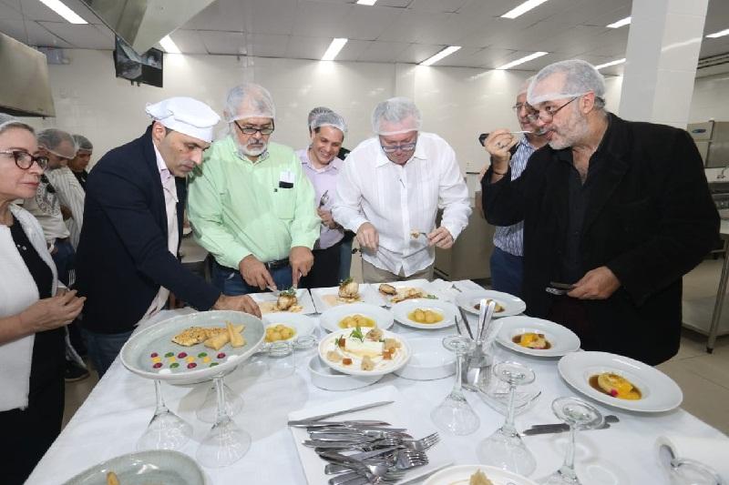 Miembros del jurado probando y degustando los platos presentados.