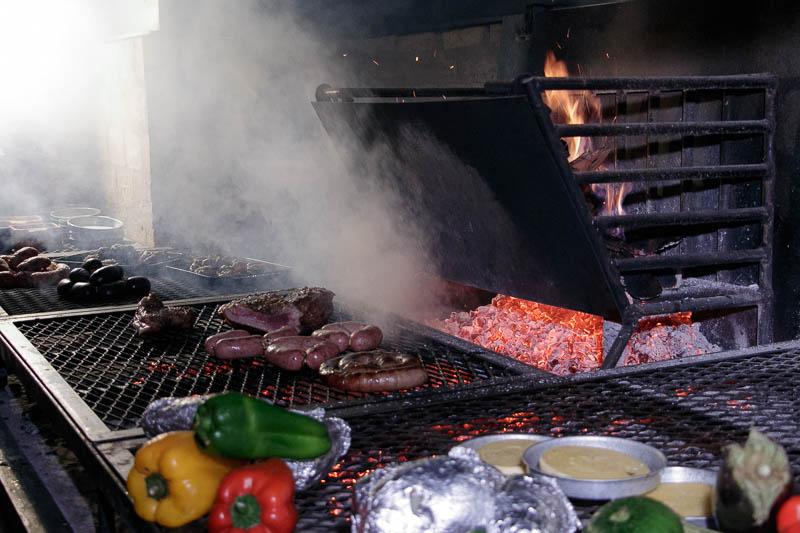 Esto es lo que define a la parrilla uruguaya. Utilizan leña y se cocina con las brasas, en una parrilla hecha con tejido de alambre. Allí van , las carnes, los embutidos, las verduras, el queso provolone, así como las papas y las batatas.