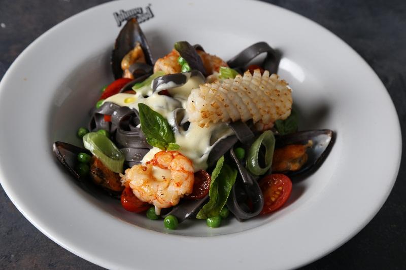 Fetuccine di mare, fetuccine con tinta de calamar, langostinos, mejillones, puerro, tomates cherry, arjeas, salsa Alfredo y pesto de rúcula.