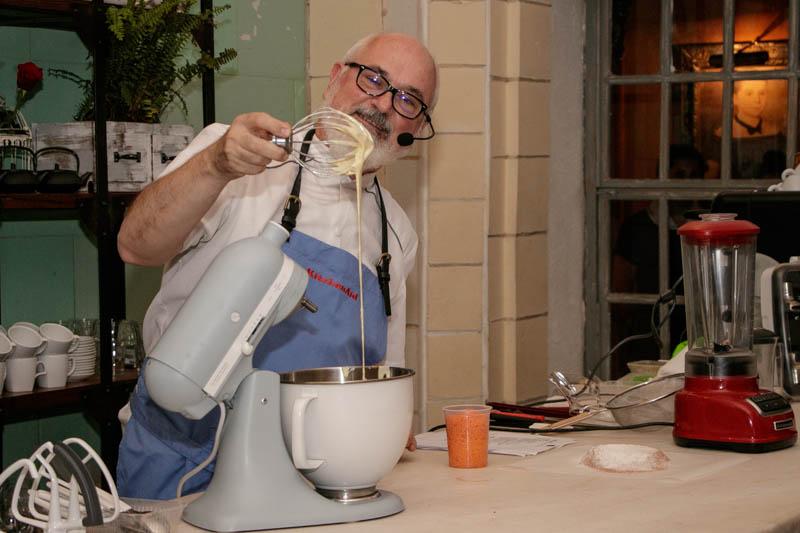 Osvaldo Gross mostrando la consistencia de la crema preparada con el pequeño robot de colos gris que tiene enfrente. NGO conmemoró así los 100 de la batidora KitchenAid.