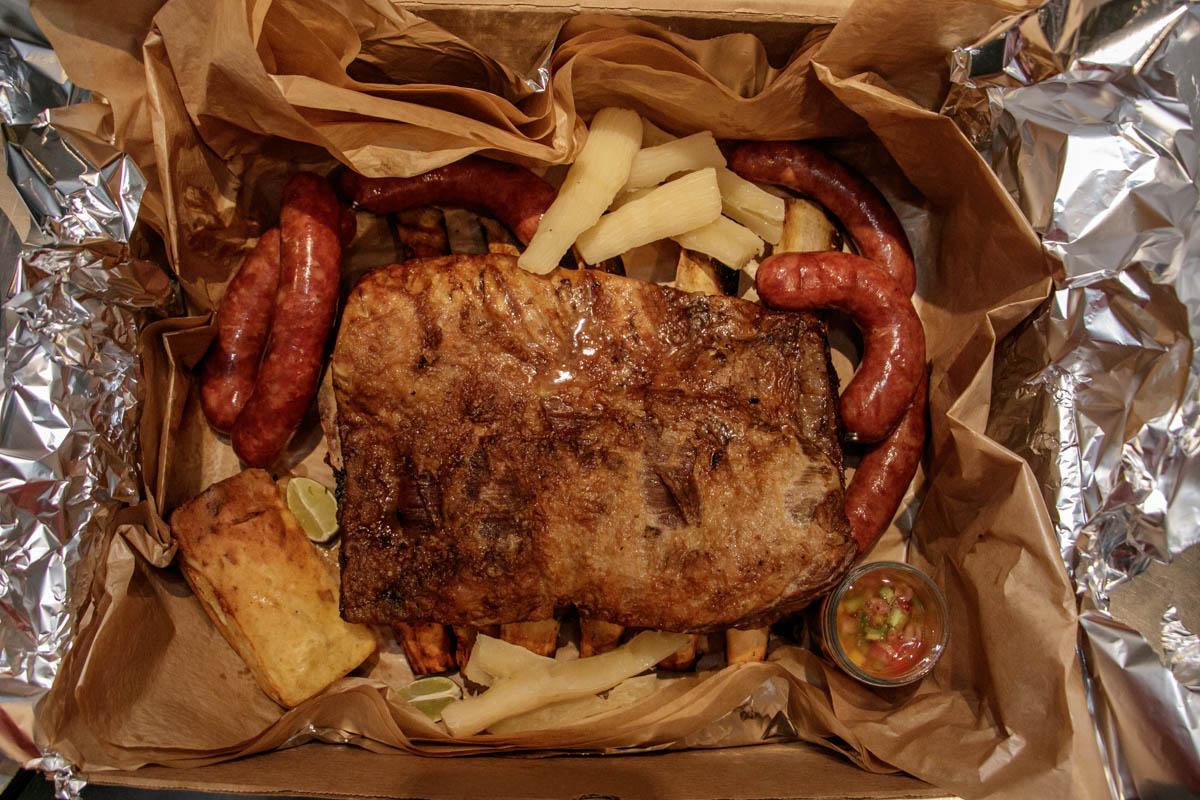 La Caja de Pozo. Alli se incluuyen, 5 kilos de asado, 1 pollo entero, 1 kilo de chorizos artesanales, chipa guazu, sopa paraguaya, ensalada verde y mandioca.